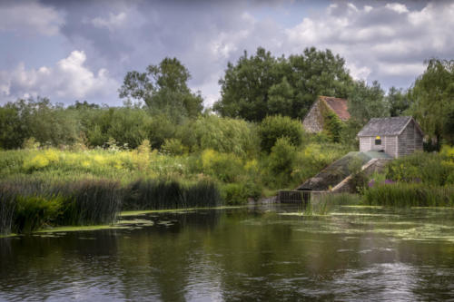 the river stour at fiddleford mill with clouds and reflections in river