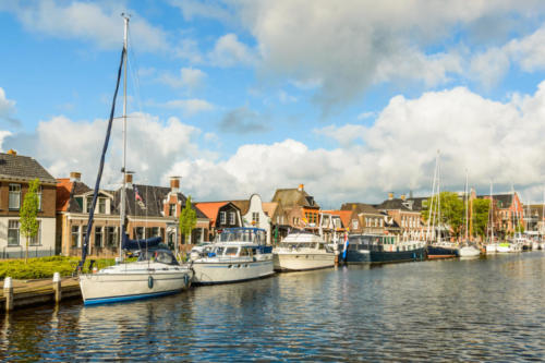 Dutch canal with moored boats on the shore, city of Lemmer.